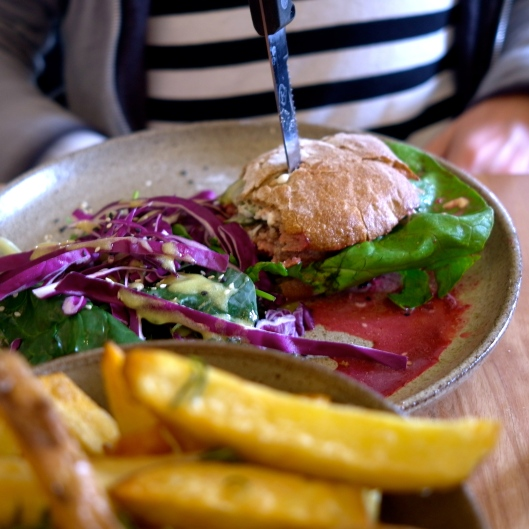 Grass fed burger, beetroot relish, butter lettuce, pickles and aioli (but sans cheddar) served with a bowl of hand cut chips with crisp herbs Please note the beetroot juice is only like that because LM has already had a hefty bite out of his burger! (Image by TSL)